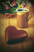 Chocolate heart lying on a wooden table with a cup of coffee and a bouquet, сердце — Stock Photo