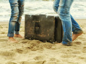 Male and female feet on the sand near the sea with a leather suitcase — Stock Photo