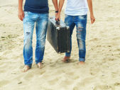 Male and female feet on the sand near the sea with a leather suitcase, image in the sunny  trendy vintage style — Stock Photo