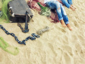 Legs in jeans, men and women lying on a plaid blanket on the sand on the beach with a valise, mesh, anchor chain and bouquet, image in the sunny  trendy vintage style — Stock Photo