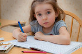 Baby girl sitting writing at the table — Stock Photo