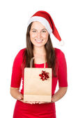 Pretty brunette woman in christmas outfit holding present — Stock Photo