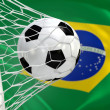 Brazil waving flag and soccer ball in goal net — Stock Photo #36935553