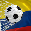 Colombia waving flag and soccer ball in goal net — Stockfoto