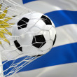 Uruguay waving flag and soccer ball in goal net — Stock Photo