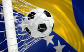 Bosnia and Herzegovina waving flag and soccer ball in goal net — Stock Photo