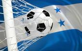 Honduras ondeando bandera y fútbol bola en meta neto — Foto de Stock