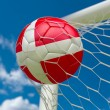 Denmark flag and soccer ball in goal net — Stock Photo