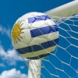 Uruguay flag and soccer ball in goal net — Stock Photo