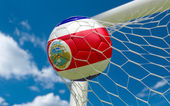 Costa Rica flag and soccer ball in goal net — Stock Photo