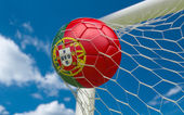 Portugal flag and soccer ball in goal net — Stock Photo