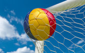 Romania flag and soccer ball in goal net — Stock Photo