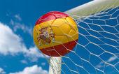 Espanha bandeira e futebol a bola na baliza líquida — Fotografia Stock