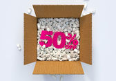 Box with shipping peanuts and 50 percent off sign — Stock Photo