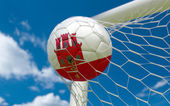 Gibraltar flag and soccer ball in goal net — Stock Photo