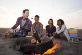 Two Young Couples Around a Fire on the Beach — Stock Photo