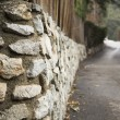 Forest mountain road and stone wall, close-up — Stock Photo #36740045