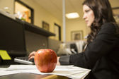 An apple on a desk — Stock Photo