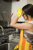 Fatigued woman cleaning dishes — Stock Photo