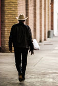 Lonely cowboy walking down the sidewalk — Stock Photo