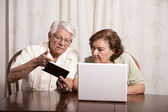 Elderly couple with checkbook and laptop — Stock Photo