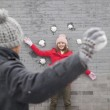 Man throwing snow balls at young woman on wall — Stock Photo #36085431