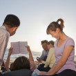 Multigenerational family relaxing and reading on the beach — Stock Photo