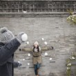 Man throwing snow balls at young woman on wall — Stock Photo