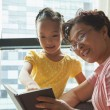 Grandmother reading book to her granddaughter — Stock Photo