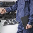 Businessman shaking hands with Mechanic — Stock Photo #36081781