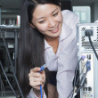 Businesswoman Plugging Cord Into Back of Computer — Stock Photo #36081797
