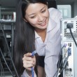Businesswoman Plugging Cord Into Back of Computer — Stock Photo