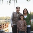 Family portrait with fishing gear at a lake — Stock Photo #36083301
