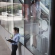Young businesswoman inside the building talking on the phone, another women outside of the building looking at her notes — Stock Photo #36083567