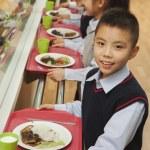 School children standing in line in school cafeteria — Stock Photo #36084373
