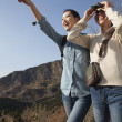 Women hiking, pointing at the mountain top — Stock Photo