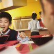School boy eating noodles in school cafeteria — Stock Photo #36087595