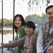 Family portrait with fishing gear at a lake — Stock Photo