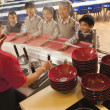 School cafeteria worker serves noodles to students — Stock Photo