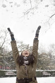 Woman throwing snow into air in park — Stock Photo