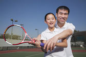 Young girl playing tennis with her coach — ストック写真