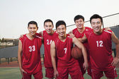 Basketball team standing and smiling, portrait — Stock Photo