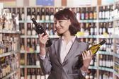 Mid Adult Woman Choosing Wine in a Liquor Store — Stock Photo