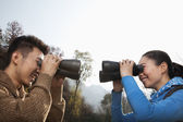 Couple looking at each other through binoculars — Stock Photo