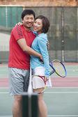 Couple into the tennis net — Stock Photo