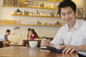 Portrait of young man working at a coffee shop — Stock Photo
