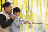 Grandfather and grandson fishing portrait at lake — Stock Photo