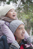 Father carrying daughter in winter — Stock Photo