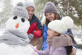 Family making snowman in winter — Stock Photo