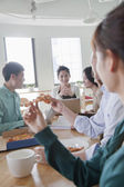 Coworkers eating and working in the cafeteria — Stock Photo